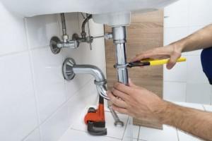 A man takes apart a drain.