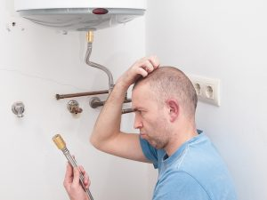 Confused-looking man stares at plumbing part and scratches his head