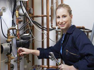 Plumber smiling at camera as she makes pipe repair