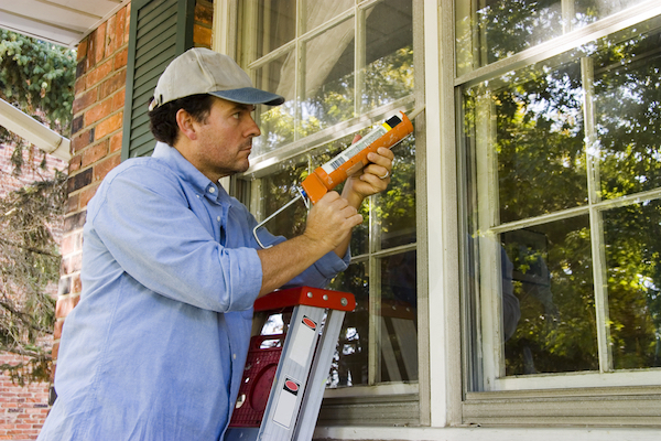 Man on ladder using caulking gun to seal window