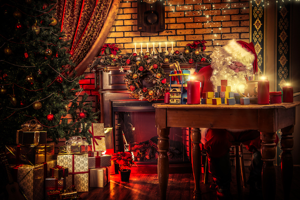 Santa sitting at table with head down. Table covered in candles and toys. Fireplace behind Santa, Christmas tree to his left. Presents beneath tree.