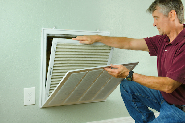 Man replacing air filter from air vent