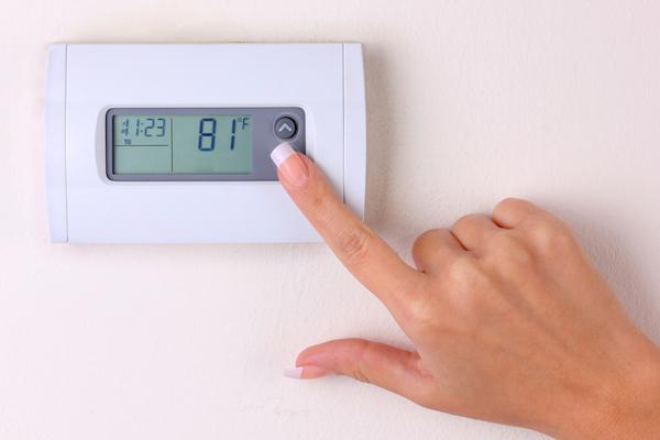 Woman programming digital thermostat