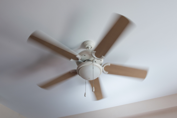 Ceiling fan with wooden blades in a white room