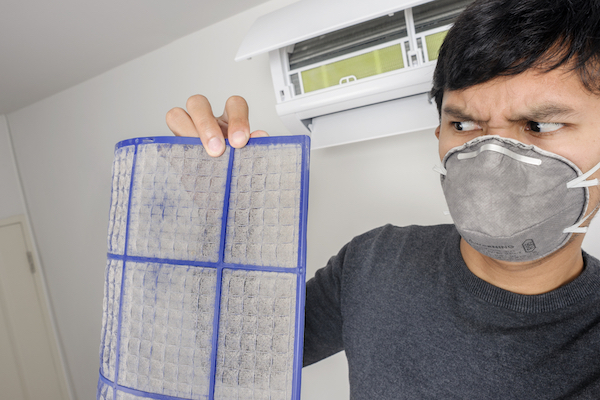 Man in face mask holding dirty air filter and looking at it with disgust