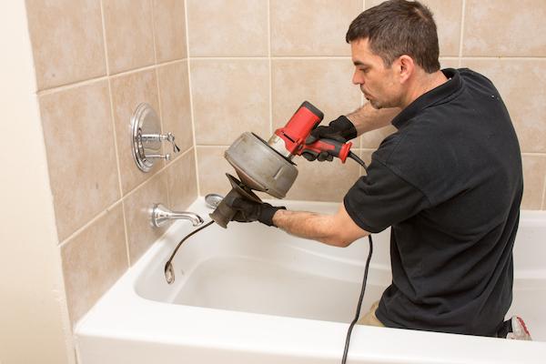 Plumber using auger on bathtub
