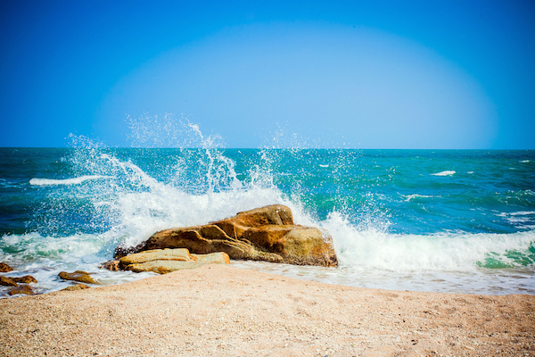 Waves breaking on a brown rock near a shoreline on a bright day. Water hammer.