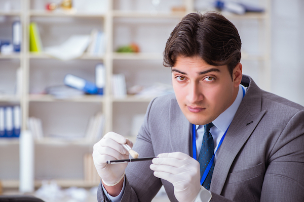 Man in suit wearing surgical gloves dusts a pen with a forensic brush