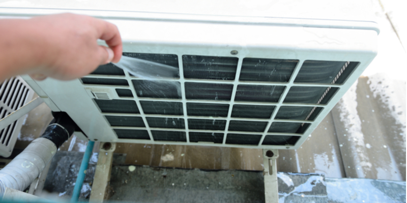 Cleaning out the front of an air conditioner's condenser unit