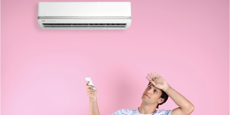 Sweating, uncomfortable-looking man tries to turn on his indoor air conditioner