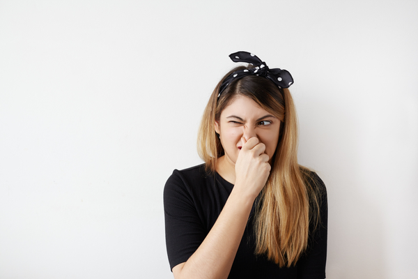 Woman holding her nose after smelling stinky plumbing problems