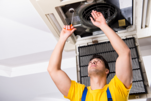 Technician prepares an HVAC system for spring with an inspection