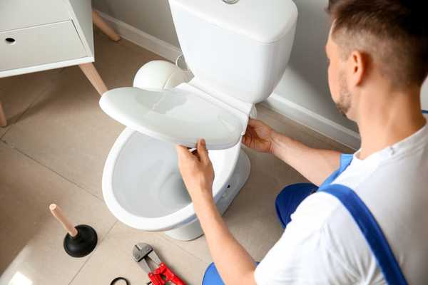 Plumber working on installing a new toilet in a bathroom