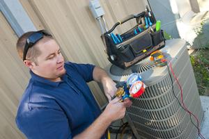 A repairman examines a air conditioning unit.